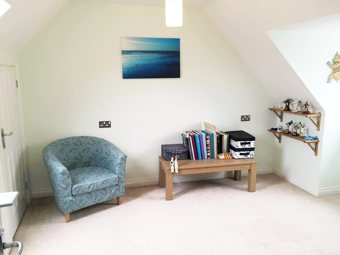 my spare room with a chair and table and shelves
