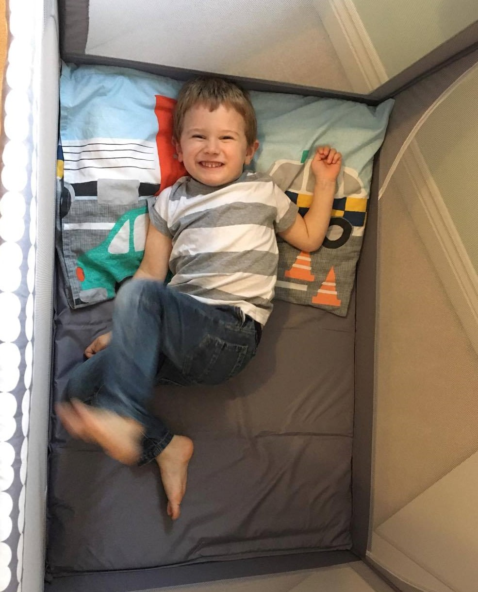 boy in travel cot