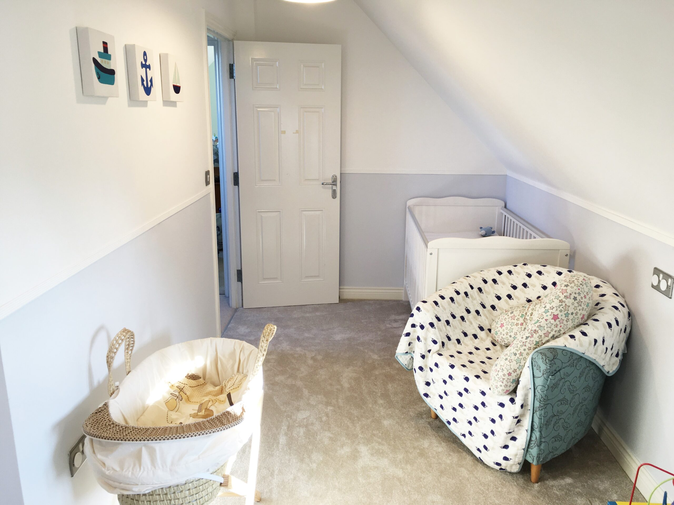 baby's nursery with cot, moses basket and chair