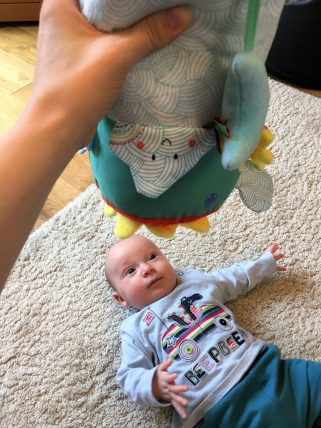 baby on floor with sensory toy above him