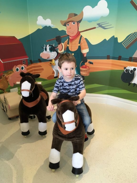 Jake on a toy horse at little play town