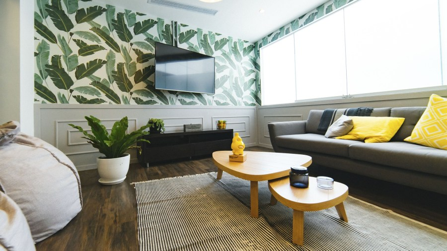 living room with trends like boldcolours and leaf print wallpaper