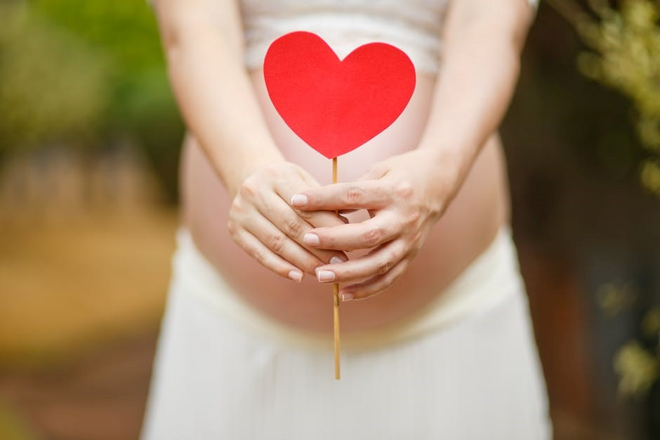 pregnant lady holding a heart