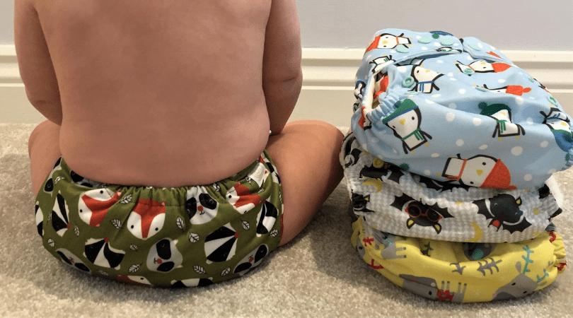 change to cloth nappies baby wearing cloth nappy with three more cloth nappies next to him
