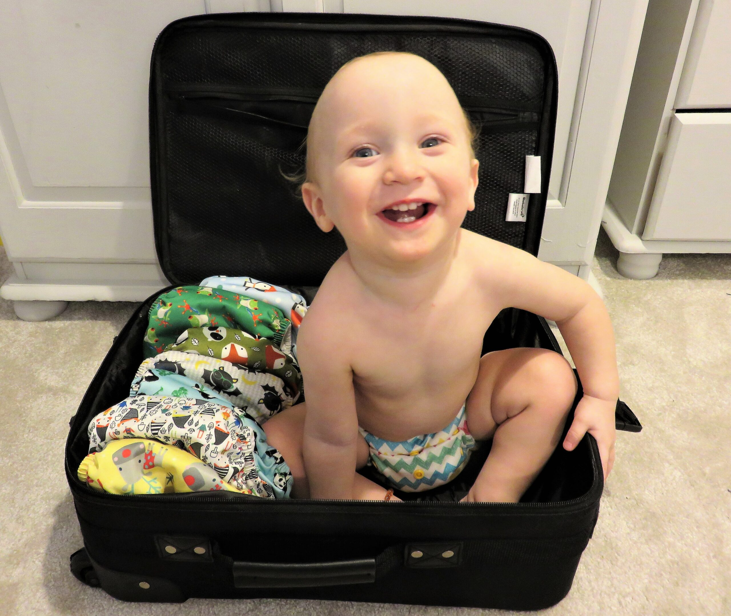 baby sat in a suitcase with reusable nappies