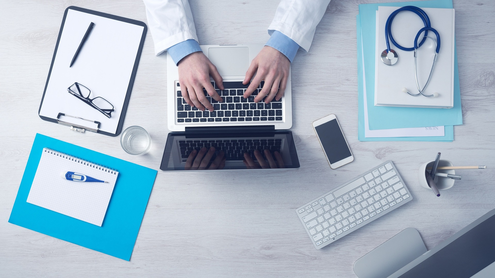 doctors hands at a desk with laptop and note books