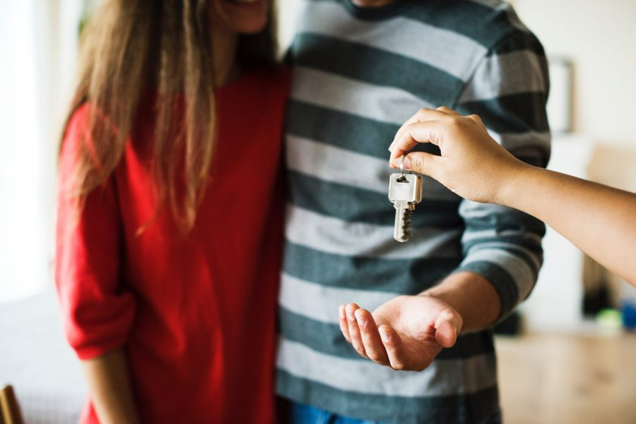 couple being handed a key to their new home