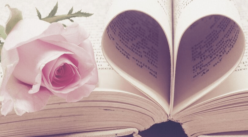 book folded into a heart shape with a rose next to it
