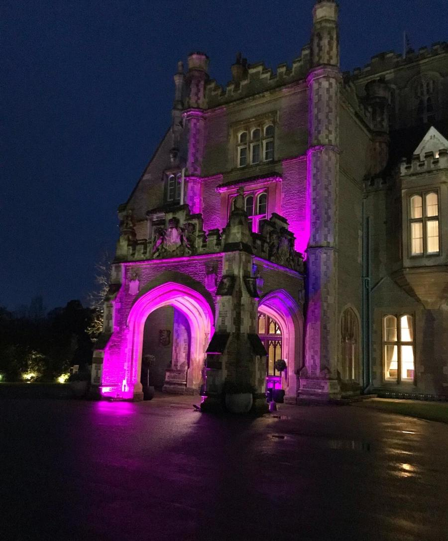 the hotel lit up at night with a pink/purple light