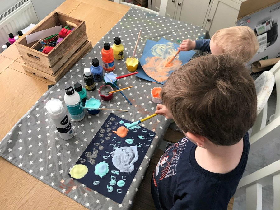 both boys using the foam to make planets