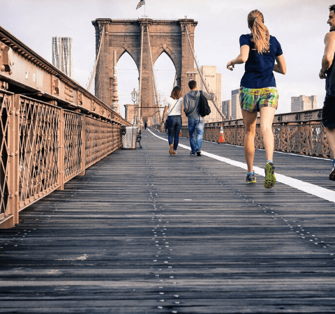 a couple running together on a bridge
