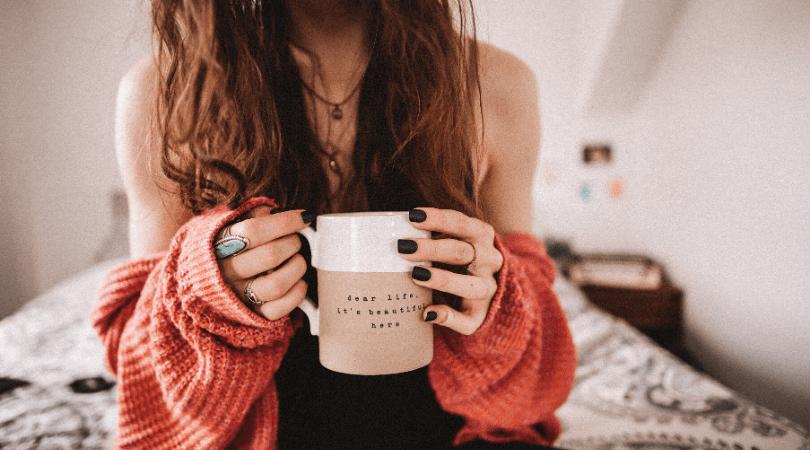a lady sat on a bed holding a mug