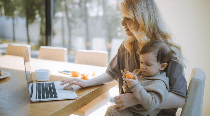 a mum holding a baby whilst looking on a laptop