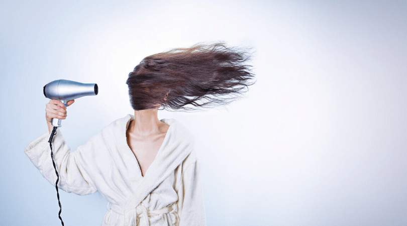 woman holding a hair dryer with hair blowing to the side