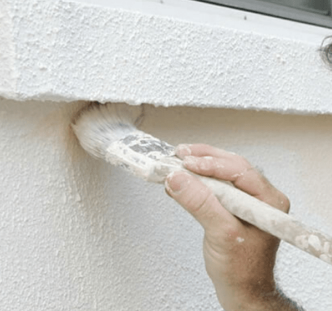 a man painting an exterior wall