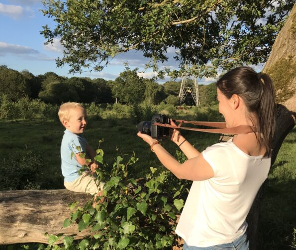 Ewa photographing William sat on a log