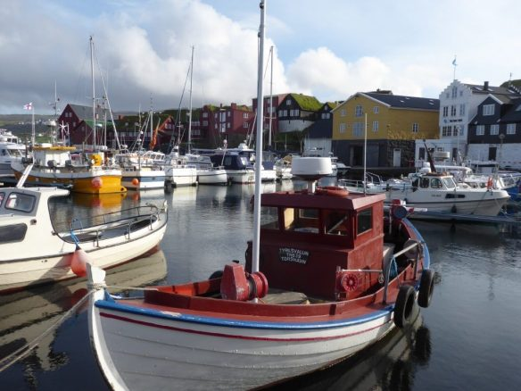 Small boats in the harbour. In the background, houses including some with grass roofs