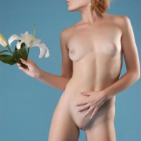Emma Watson posing nude, with bald pussy and orchid, blowing a kiss