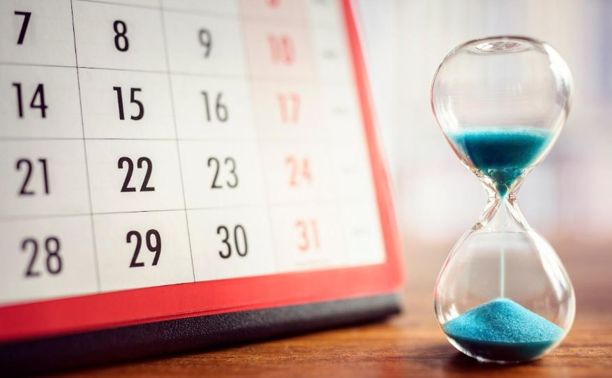 Blue hourglass and calendar on wooden table