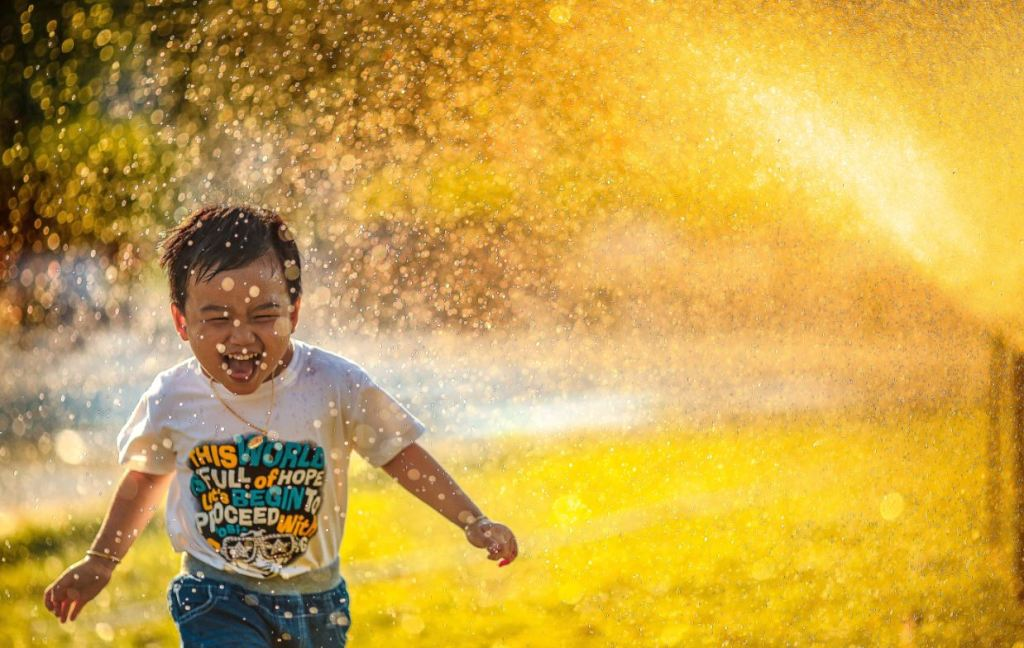 Young boy running through sprinklers laughing
