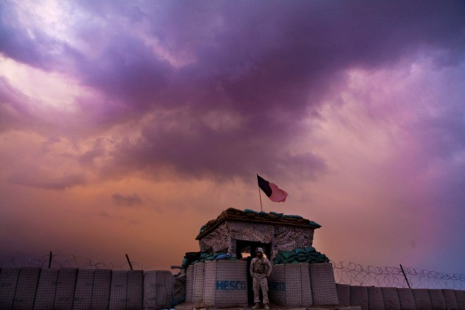 A U.S. Marine from the First Battalion Eighth Marines Alpha Company looks out as an evening storm gathers above an outpost near Kunjak in southern Afghanistan's Helmand province, February 22, 2011. REUTERS/Finbarr O'Reilly/File Photo     TPX IMAGES OF THE DAY      - RTX2K2IW