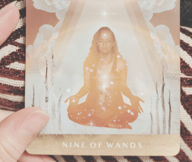 A hand holds an orange tarot card, the nine of wands.