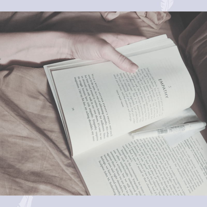 A hand with a moon tattoo holds a book on a bed, open to a chapter on empathy.