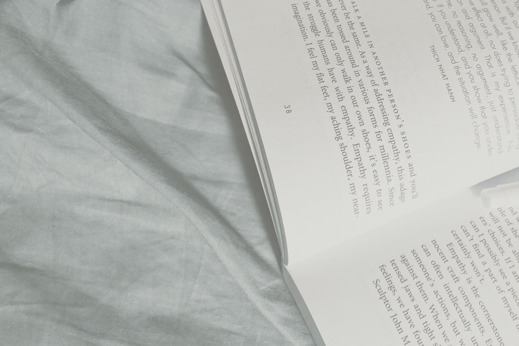 A book discussing empathy and mindfulness lays on a bed with light blue sheets