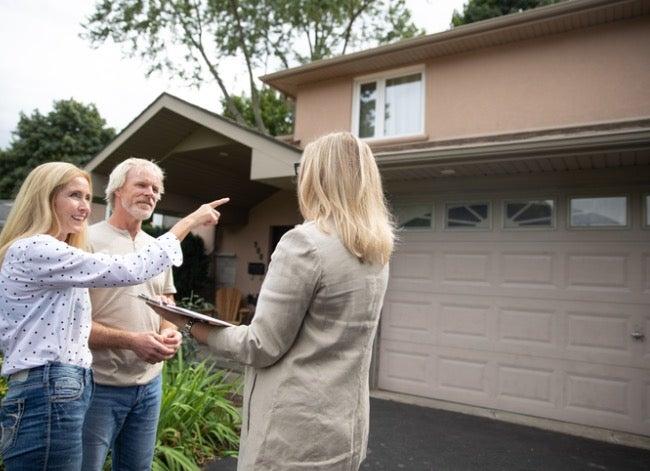 Paar mit Immobilienmakler, der Haus betrachtet