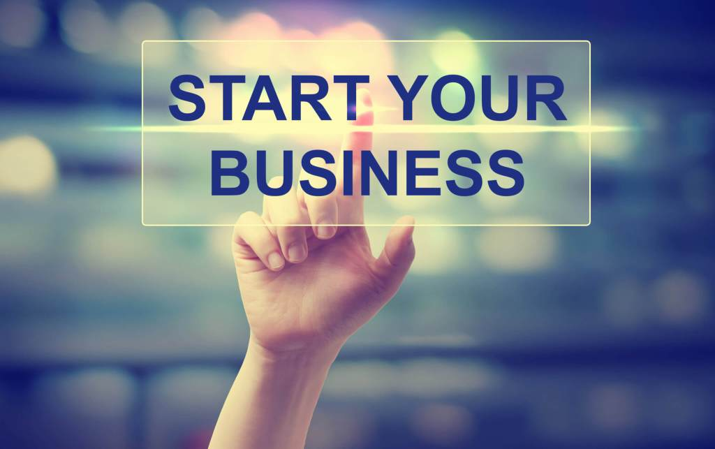 Hand pressing Start Your Business on blurred cityscape background
