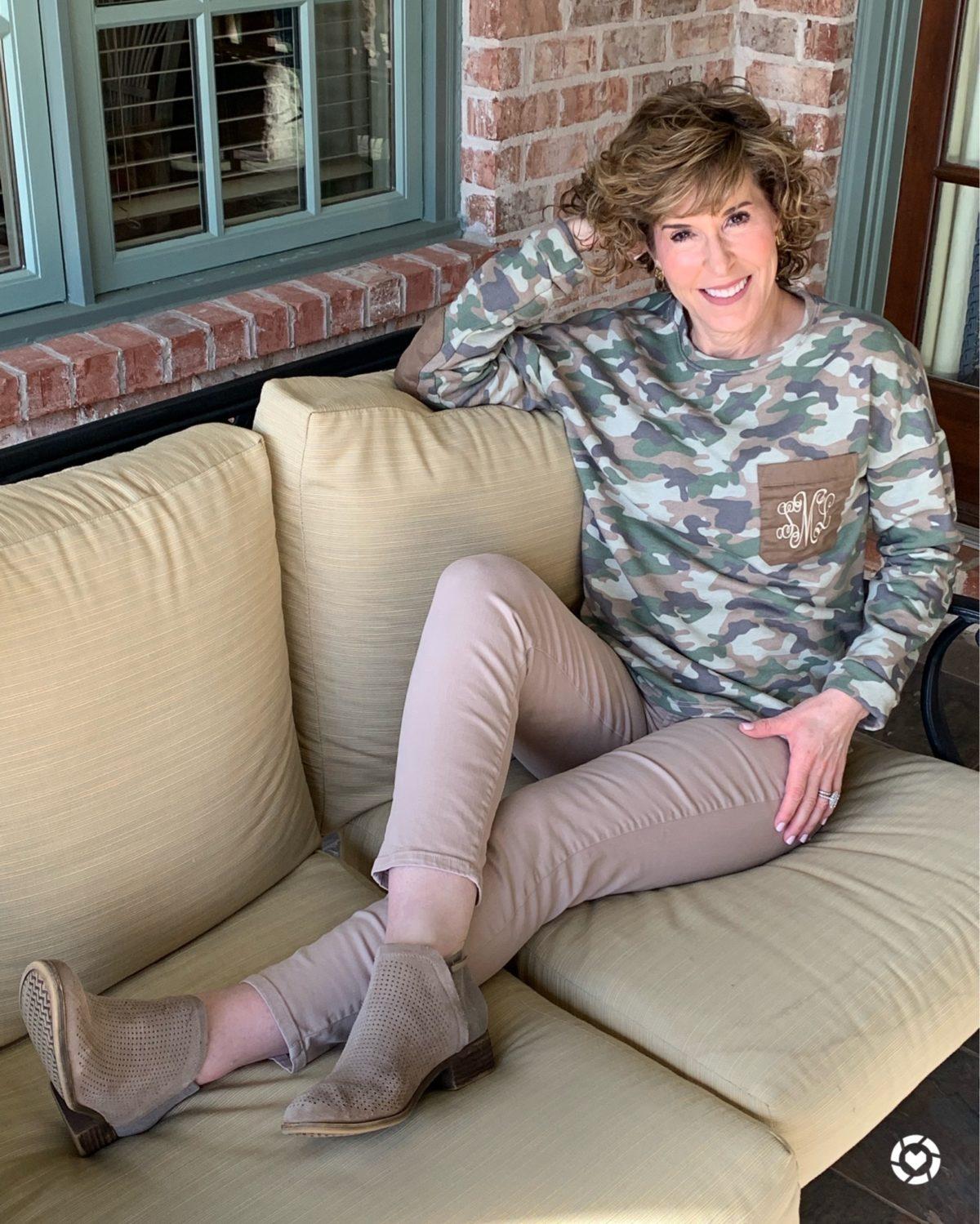 woman wearing camo monogram sweatshirt lounging on sofa