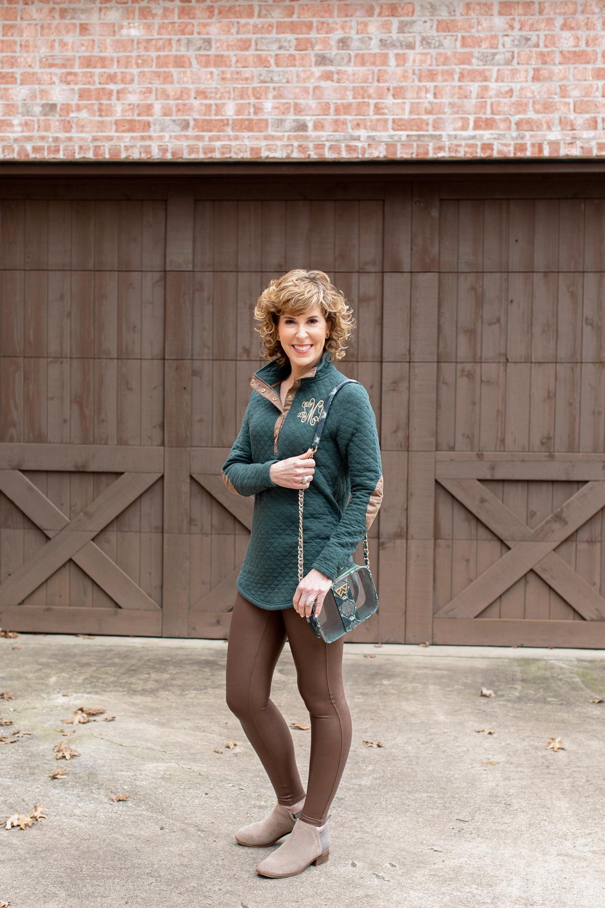 woman in green monogrammed sweatshirt standing on driveway