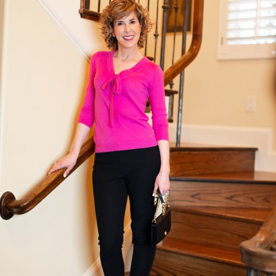 woman in pink bow sweater standing on staircase