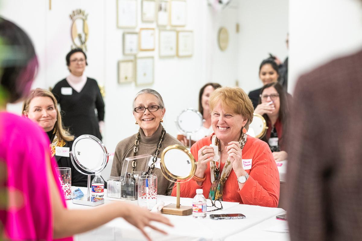 women laughing in makeup class