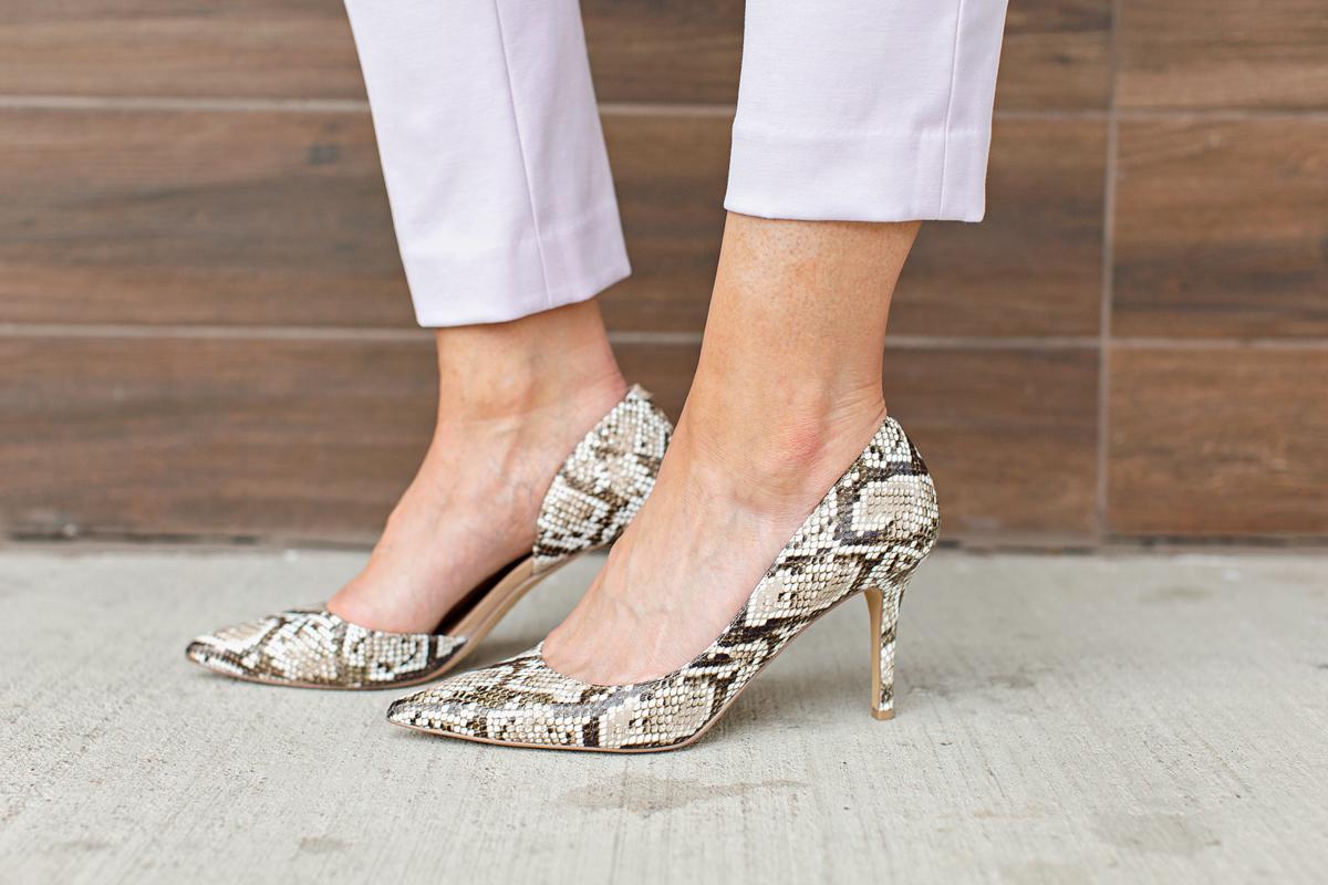 snakeskin pumps on woman's feet