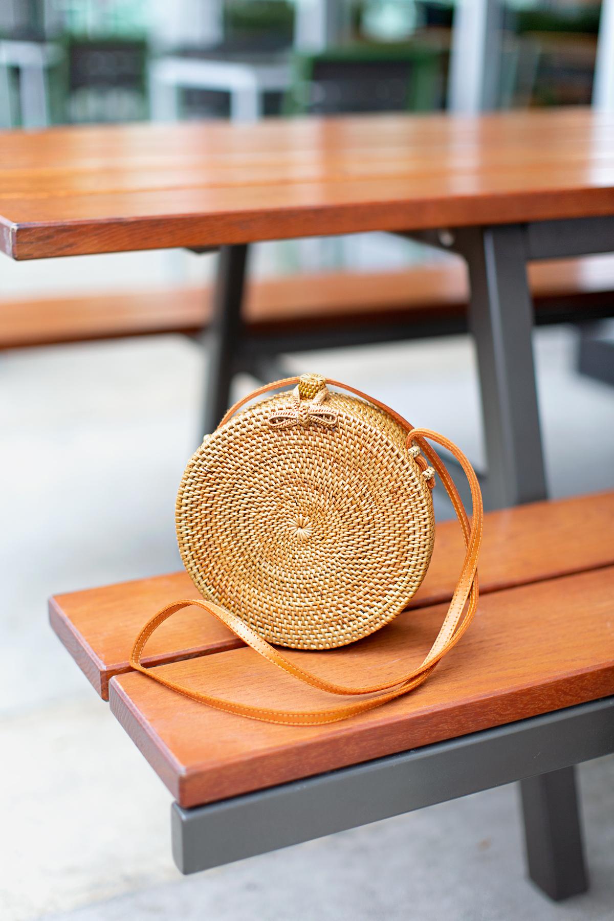 rattan circle handbag on a bench