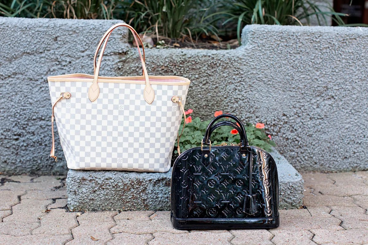 two designer handbags sitting on the ground