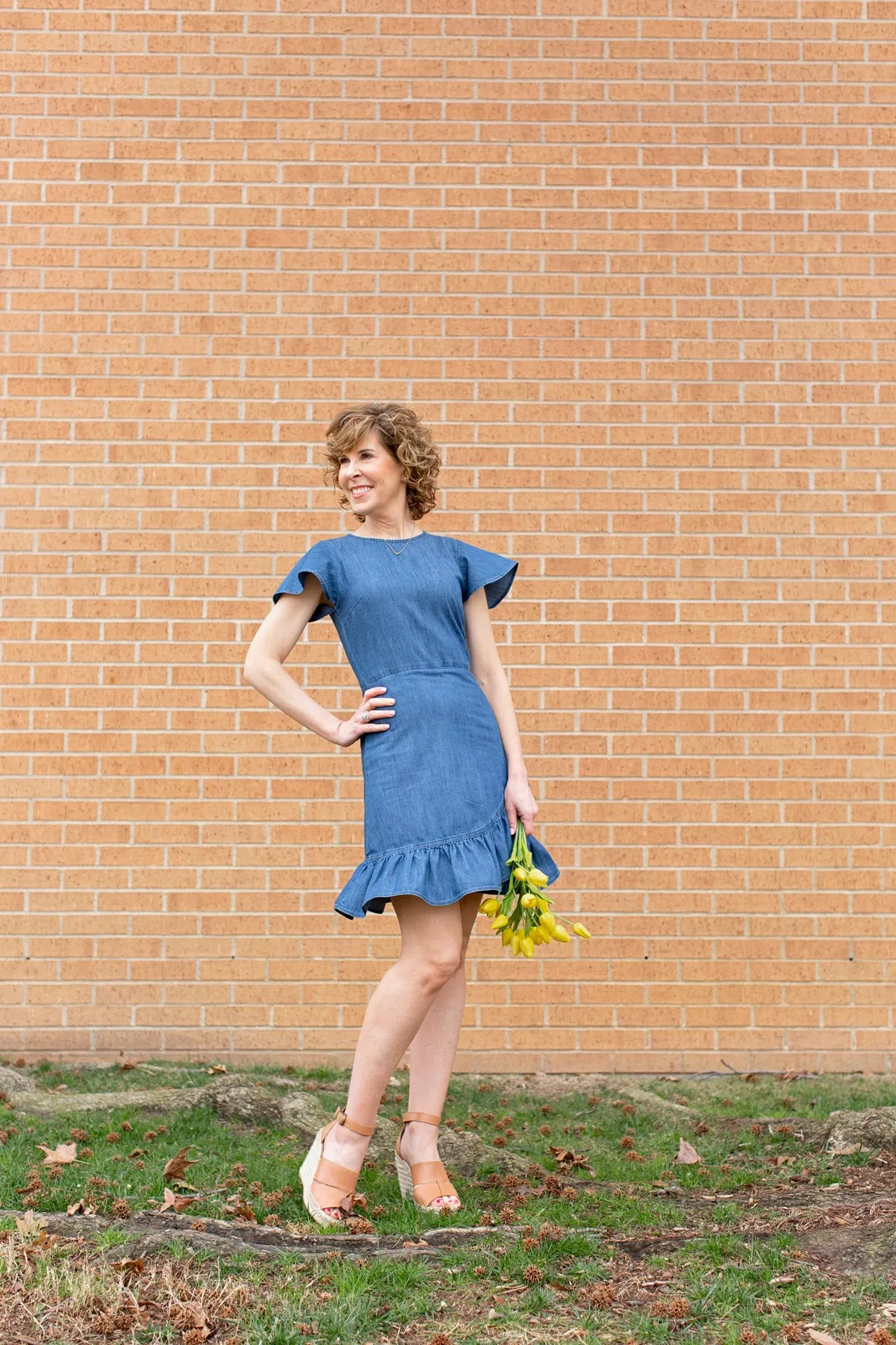 woman in blue dress holding yellow flowers and looking to the side