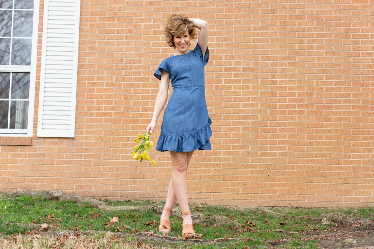 woman in blue dress holding her hair and yellow flowers
