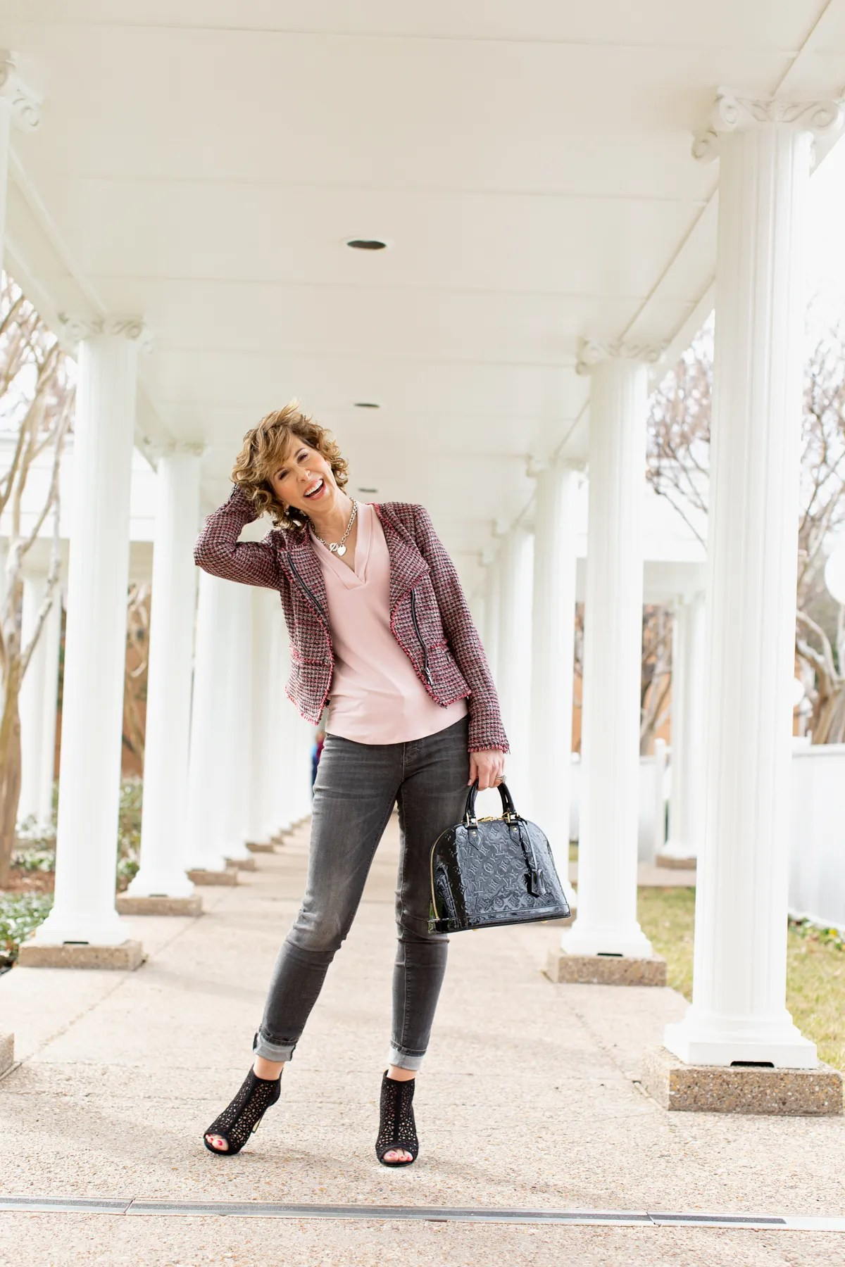 woman in black and pink outfit standing outside among white columns
