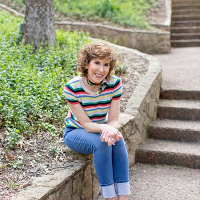 woman in striped sweater seated on stone wall in park