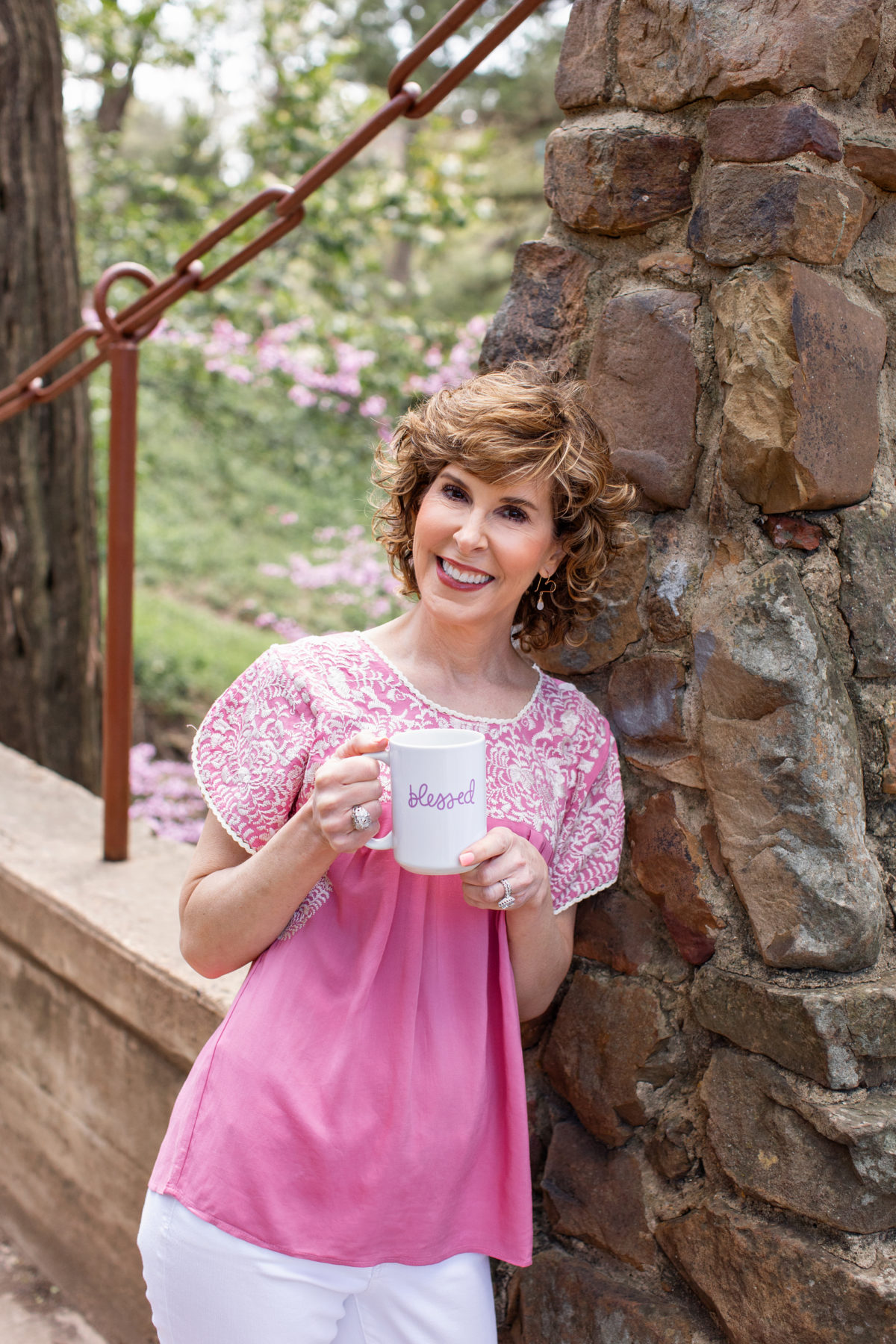 woman in pink top standing on a stone bridge holding a coffee cup