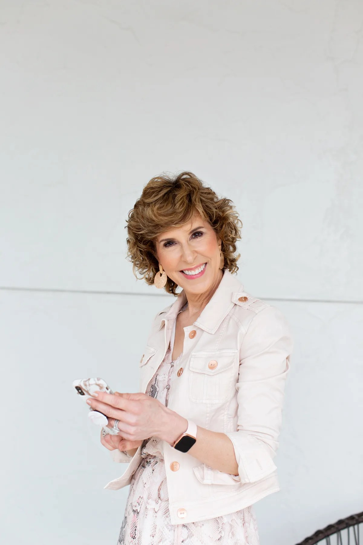 woman wearing blush jacket holding her phone and looking at camera