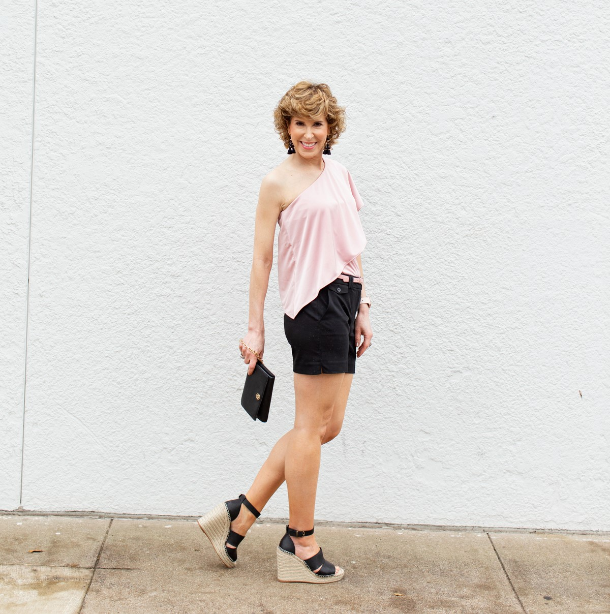 woman wearing pink one shoulder top and black shorts in front of a white wall