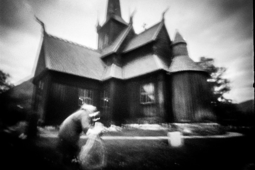 A pinhole shot of an old woman laying flowers on a grave in a Norwegian churchyard.