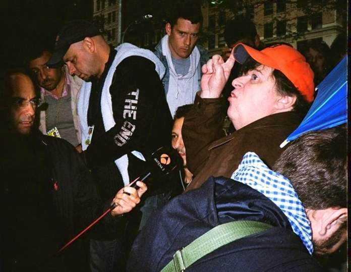 The Interview's Direction. Photographed with my Minolta Hi-Matic, & on Kodak's Gold, small-format, 135 film, 400 speed. This was during the Occupy Wall St. protesting in lower Manhattan. Filmmaker, Michael Moore was conducting an interview. I used the flash on my Minolta to photograph this frame.