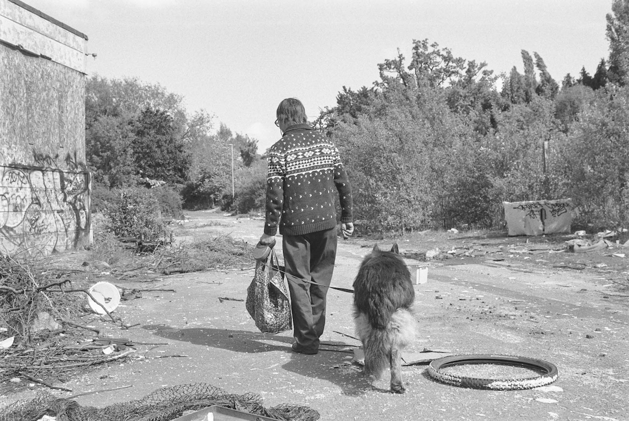 A visitor searches for valuable scrap while walking his dog. May 2017, ILFORD FP4 PLUS