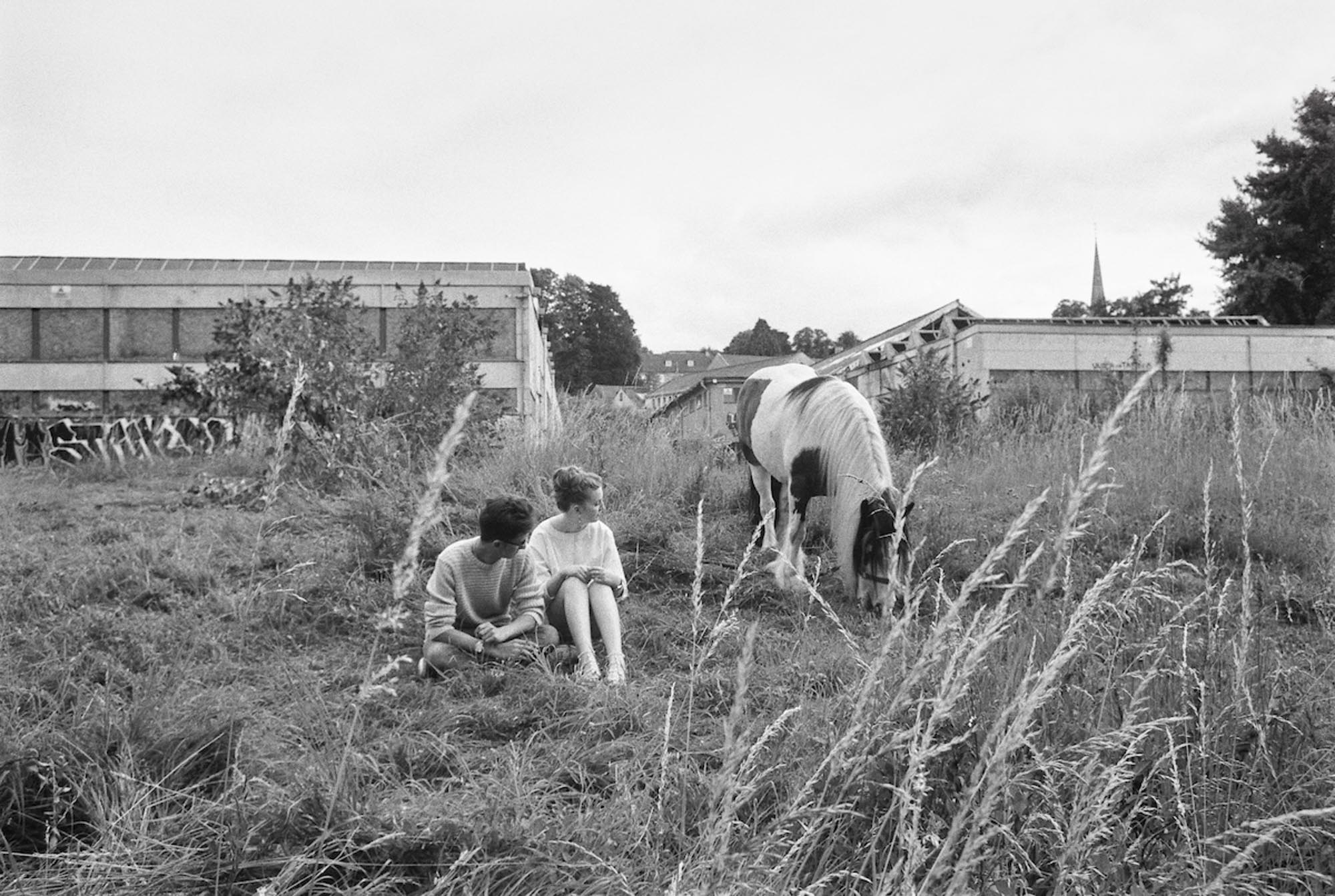 This couple visits a horse being illegally grazed on the site. July 2017, ILFORD FP4 PLUS