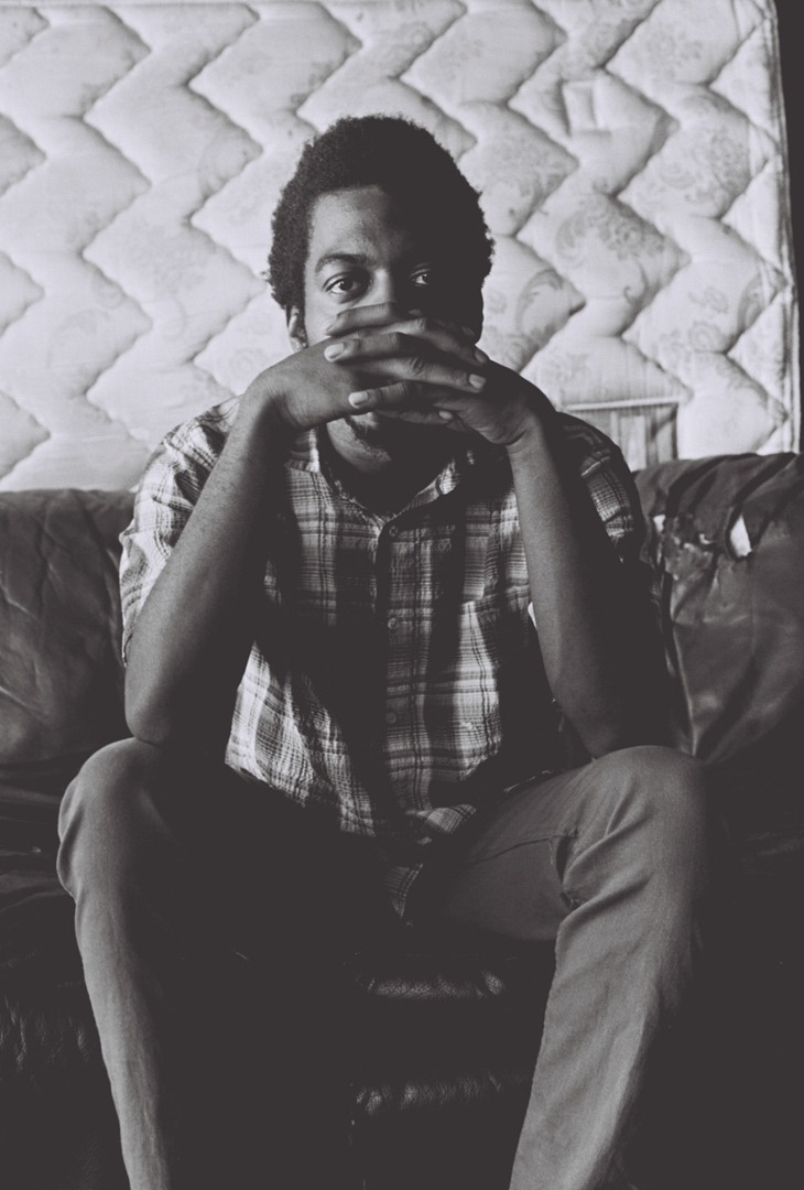 """PORTRAIT - SITTING ON COUCH Mekala Session, known as """"Mickey"""" to his friends, sits on his couch in his garage studio. He is a rising drummer synonymous with the LA underground jazz and hip-hop scene, May 2018. Shot on Kodak Tri-X 400."""