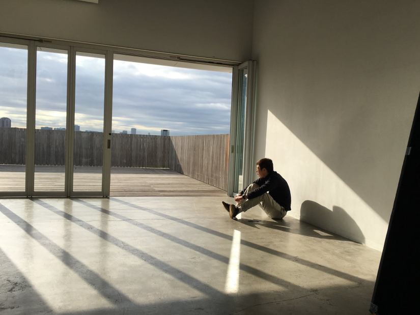 a man sits in an empty room looking out of the window